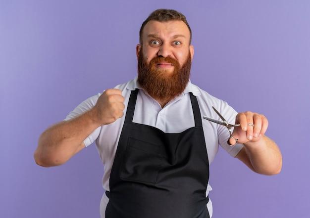 Professioneller bärtiger friseurmann in der schürze, die schere hält, die faust mit wütendem gesicht zusammenhält, das über lila wand steht
