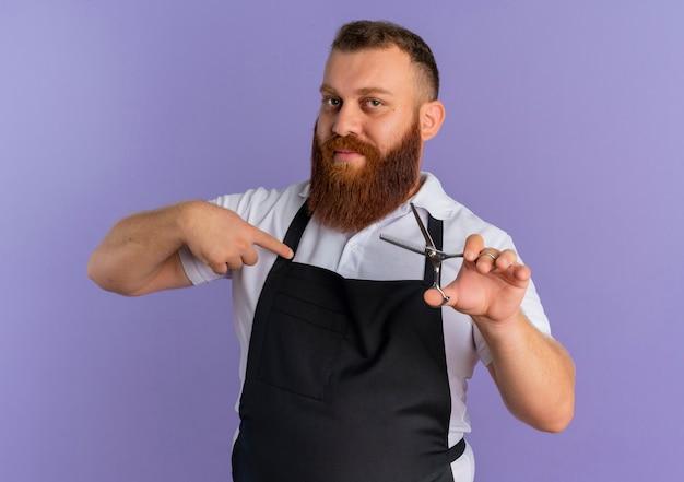 Professioneller bärtiger friseurmann in der schürze, die schere hält, die mit dem finger darauf zeigt und zuversichtlich steht, über lila wand zu stehen