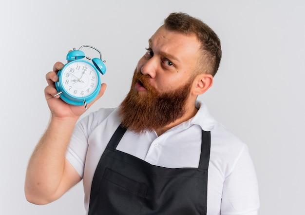 Professioneller bärtiger friseurmann in der schürze, die wecker mit skeptischem ausdruck zeigt, der über weißer wand steht