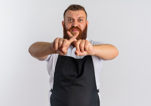 Professioneller bärtiger friseurmann in der schürze mit wütendem gesicht, das stoppschild kreuzt zeigefinger, die über weißer wand stehen