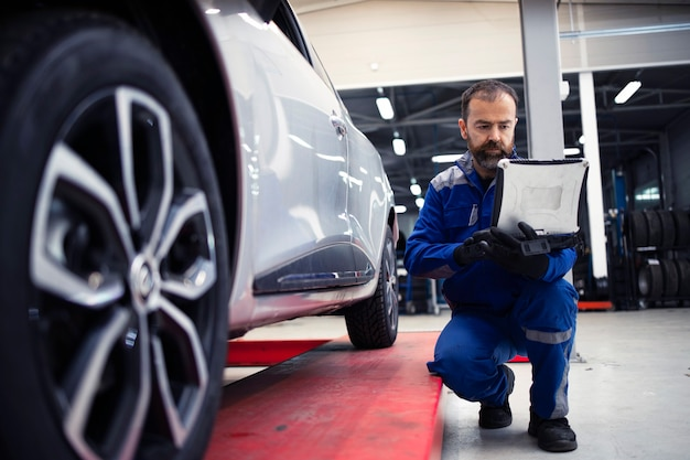 Professioneller bärtiger kaukasischer automechaniker mittleren alters, der das fahrzeug in der werkstatt und im diagnosewerkzeug visuell inspiziert.