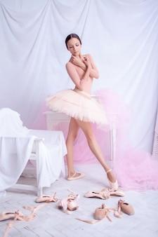 Professioneller balletttänzer, der auf rosa aufwirft