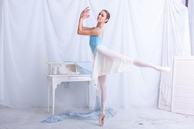 Professioneller balletttänzer, der auf weißem raum aufwirft