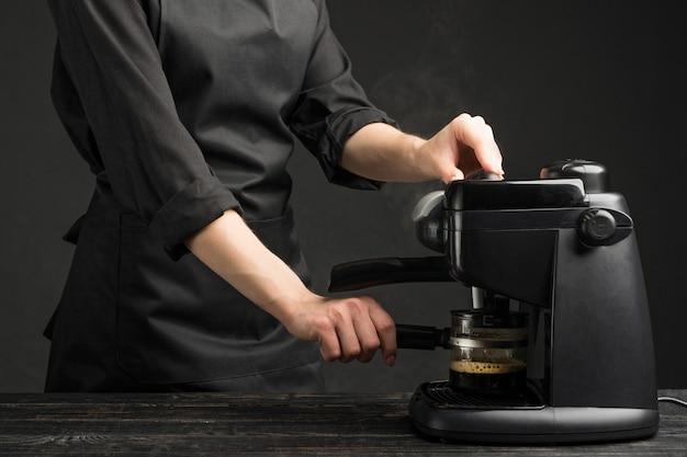 Professioneller barist mit kaffeemaschine, braut kaffee.