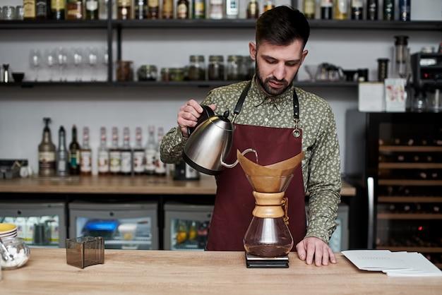 Professioneller barista, der kaffee mit chemex zubereitet, über kaffeemaschine und wasserkocher gießen. alternative möglichkeiten, kaffee zu kochen. coffee-shop-konzept.