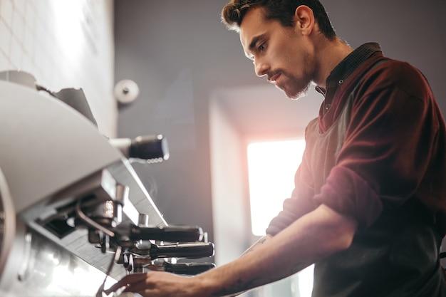 Professioneller barista, der mit kaffeemaschine arbeitet