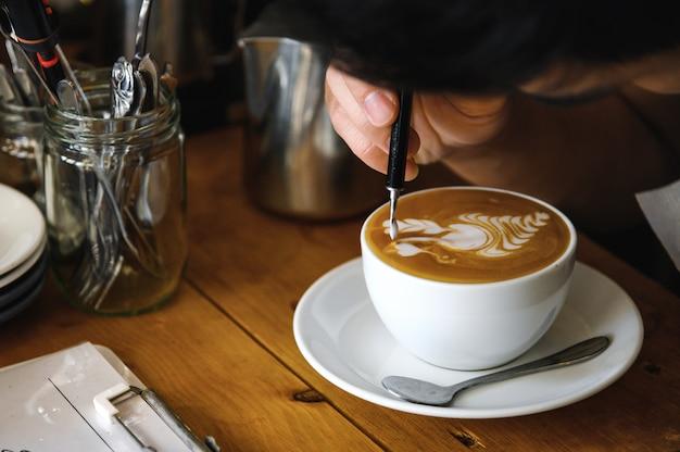 Professioneller barista, der schöne lattekunst macht