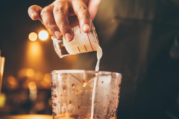 Professioneller barista macht ein frisches getränk mit tee und milch auf der tasse, trinkt leckeres bar-café, hält milchlatte im café oder restaurant in der hand, barkeeper arbeitet in cafeteria-uniform