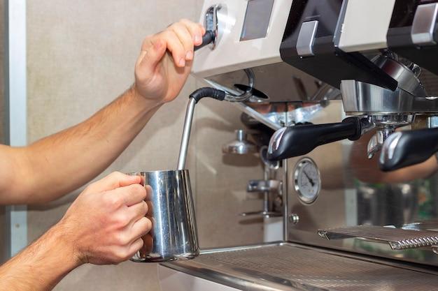 Professioneller barista mit metallkrug, der milch mit der kaffeemaschine erwärmt