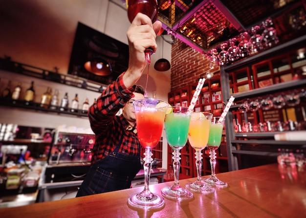 Professioneller barkeeper bereitet cocktails zu und mischt sie, indem er roten sirup aus einer flasche gießt