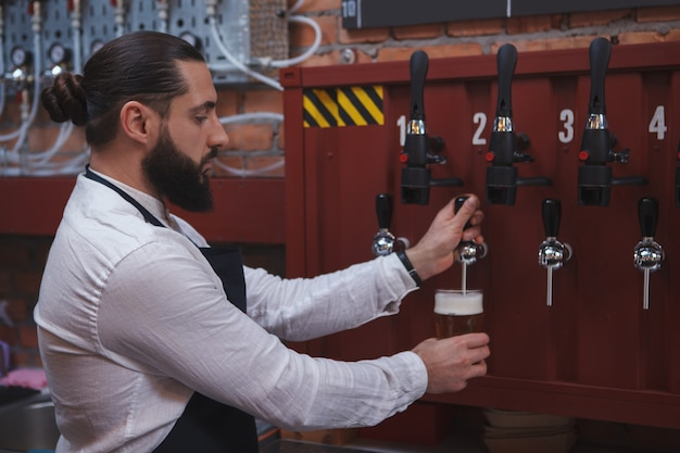 Professioneller barkeeper, der bier aus dem wasserhahn einschenkt und an seiner bar arbeitet
