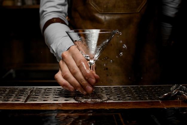 Professioneller barkeeper, der ein alkoholisches getränk im martini-glas mit einer olive mischt