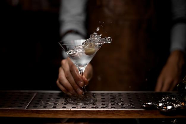 Professioneller barkeeper, der ein transparentes alkoholisches getränk im martini-glas mit einer olive mischt
