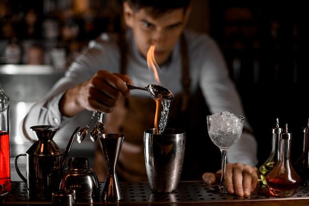 Professioneller barkeeper, der eine essenz aus dem löffel in die flamme in den stahl-shaker schüttet