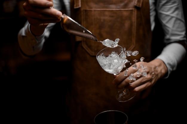 Professioneller barkeeper, der zerstoßenes eis zum glas setzt