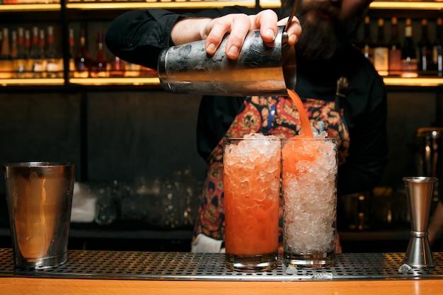 Professioneller barkeeper, der zwei cocktails macht