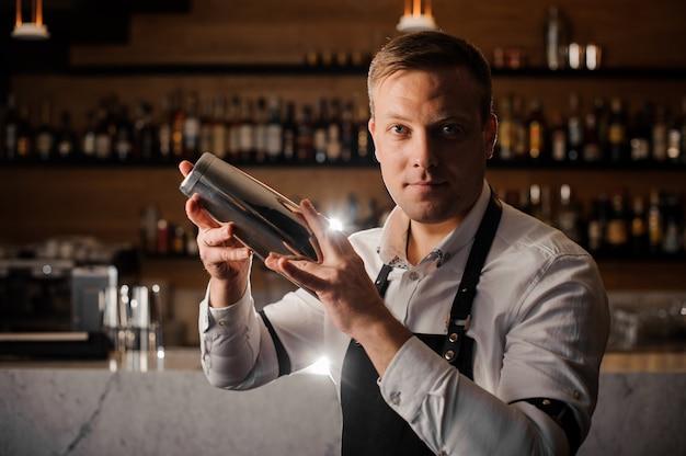 Professioneller barkeeper macht einen cocktail mit einem shaker