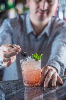 Professioneller barmann, der alkoholisches cocktailgetränk herstellt.