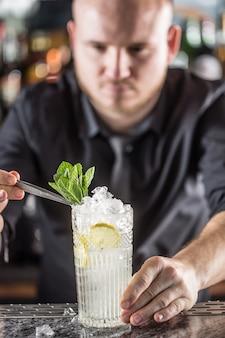 Professioneller barmann, der alkoholisches cocktailgetränk mit fruchtzucker und kräutern herstellt.