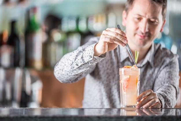 Professioneller barmann, der alkoholisches cocktailgetränk mit grapefruit herstellt.