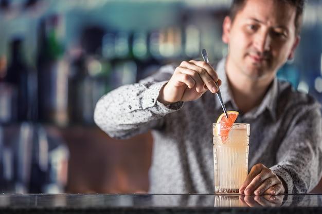 Professioneller barmann, der alkoholisches cocktailgetränk paloma herstellt.