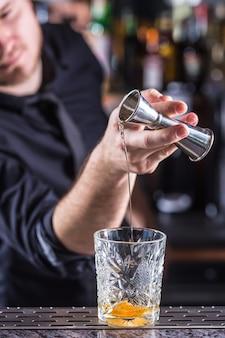 Professioneller barmann, der altmodisches alkoholisches cocktailgetränk herstellt.