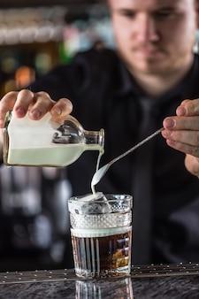 Professioneller barmann, der cocktailgetränk weiß russisch macht.