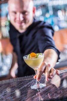 Professioneller barmann, der cocktailgetränke gefrorene margarita herstellt.