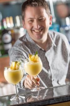 Professioneller barmann, der cocktailgetränke gefrorenen daiquiri herstellt.