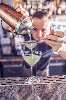 Professioneller barmann, der cocktailgetränke herstellt und alkohol einschenkt.