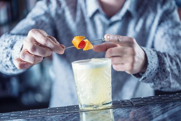 Professioneller barmann, der cocktailgetränke zubereitet und mit früchten dekoriert ist.