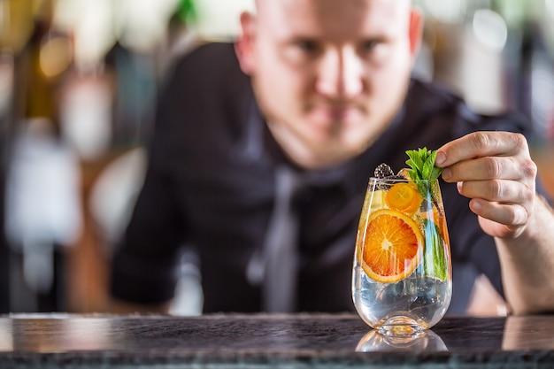 Professioneller barmann, der gin-tonic-cocktail-getränk dekoriert und mit minzkräutern dekoriert.