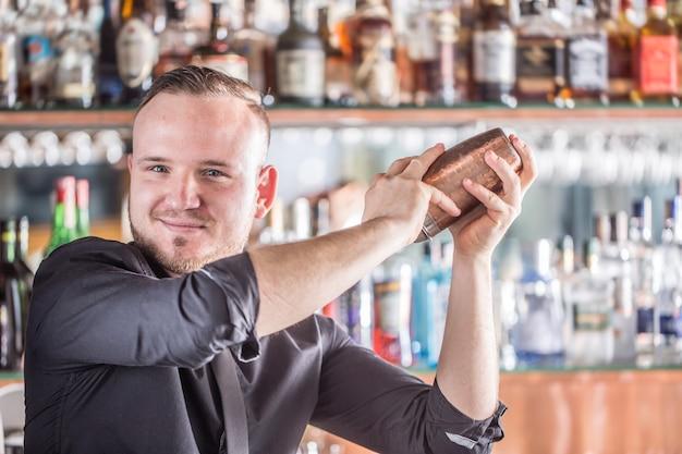 Professioneller barmann, der weißen shaker für cocktailgetränke herstellt.