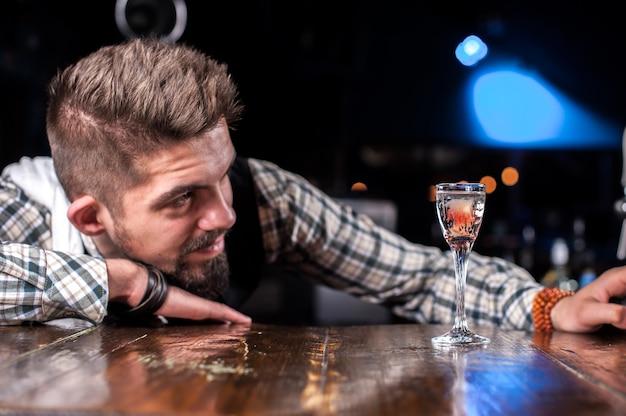 Professioneller barmann fügt einem cocktail zutaten hinzu, während er in der nähe der theke in der bar steht