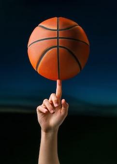 Professioneller basketballspieler, der einen ball auf handfinger dreht.