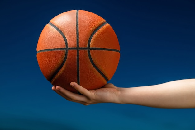 Professioneller basketballspieler, der einen ball in der hand hält.