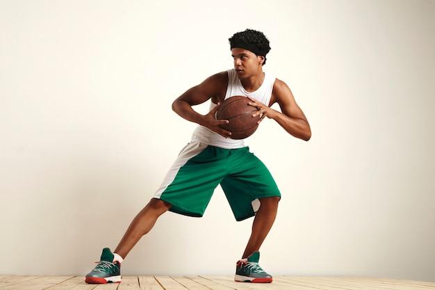 Professioneller basketballspieler, der verteidigung mit einem alten lederbasketball übt, der auf weiß isoliert wird