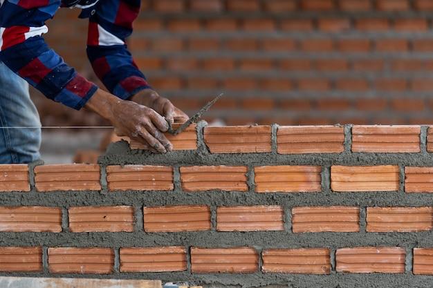 Professioneller bauarbeiter der nahaufnahmehand, der ziegelsteine im neuen industriestandort legt