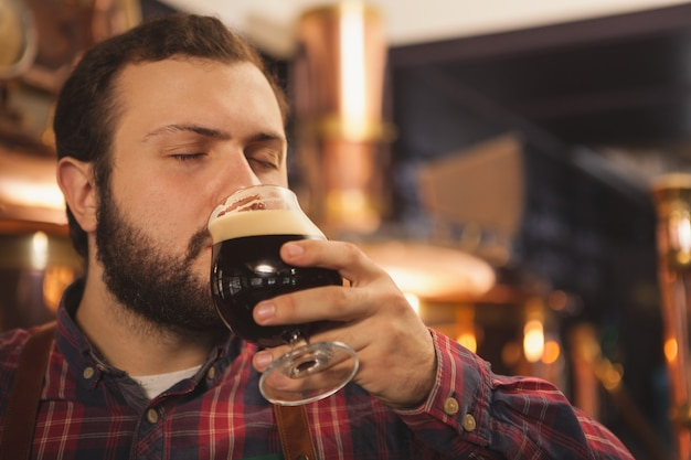 Professioneller bierhersteller, der gerne in seiner brauerei arbeitet und dunkles bier probiert