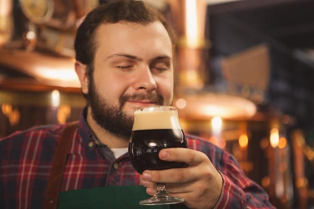 Professioneller bierhersteller, der sein leckeres craft beer genießt