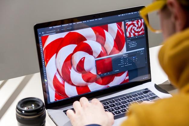 Professioneller bildbearbeiter, der an einem laptop in einer speziellen farbsoftware arbeitet