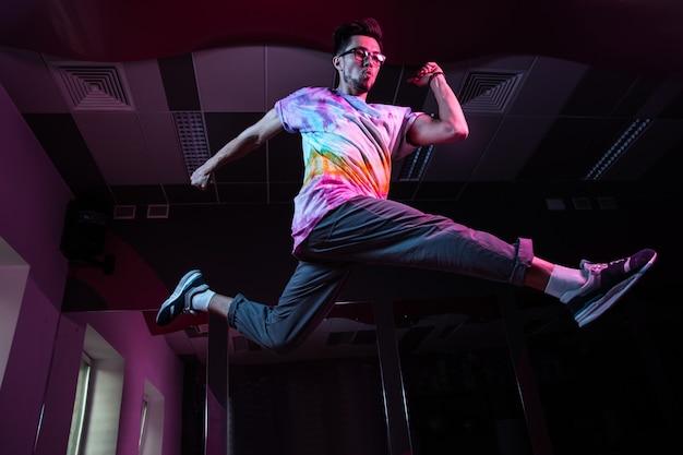 Professioneller breakdancer in bewegung, der modernen hip-hop-tanz in rosa neonlicht übt