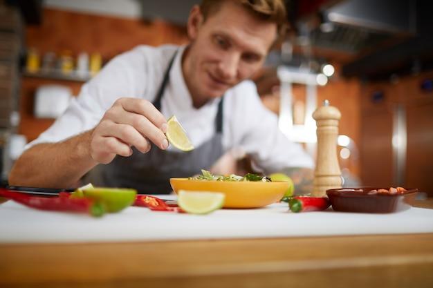 Professioneller chefkoch der nahaufnahme, der asiatisches essen serviert