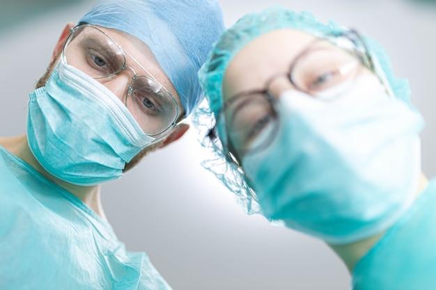 Professioneller chirurg mit einer jungen praktikantin in einem krankenhaus-op-saal aufnahme von a shot