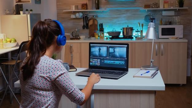 Professioneller colorist, der während der postproduktion mit videomaterial arbeitet. videograf, der audiofilmmontage auf einem modernen gerät bearbeitet, laptop sitzt auf dem schreibtisch in der modernen küche um mitternacht