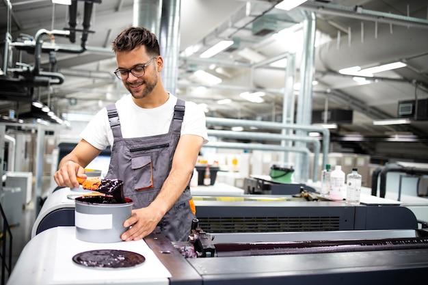 Professioneller druckmaschinenbediener, der während des druckvorgangs in der fabrik mehr farbe hinzufügt.
