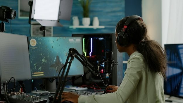 Professioneller e-sport-afro-gamer, der während des live-turniers auf microhone spricht. streamen von viralen videospielen zum aufsetzen von kopfhörern und tippen auf der tastatur während der online-meisterschaft.