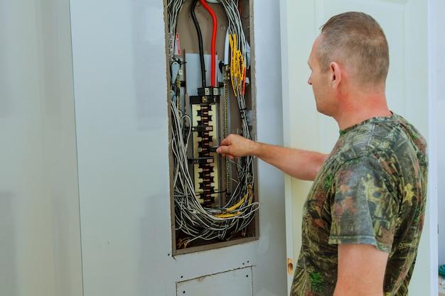 Professioneller elektriker, der komponenten im elektrischen schild installiert