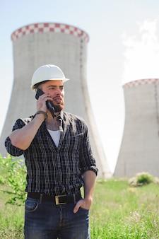 Professioneller elektrikeringenieur in einem weißen sturzhelm im workp