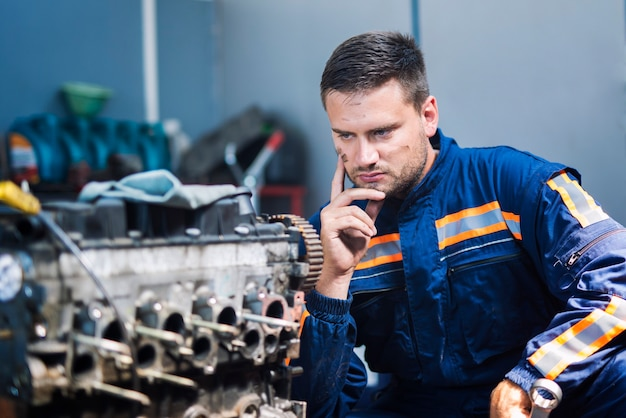 Professioneller erfahrener mechaniker-mechaniker in uniform, der über die lösung nachdenkt und den automotor in der mechanikerwerkstatt betrachtet